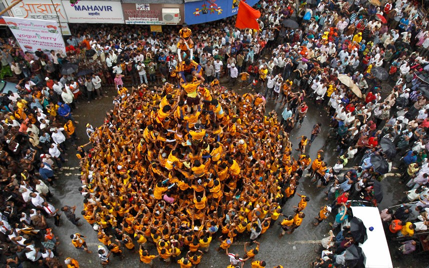 "Devotees form a human pyramid to break the ""Dahi handi,"" an earthen pot filled with curd, an integral part of celebrations to mark Janmashtami in Mumbai, India, Friday, Aug 10, 2012. Janmashtami is the festival that marks the birth of Hindu God Krishna. (AP Photo/Rafiq Maqbool)"